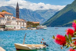 Scenic panorama view of the historic town of Perast at famous Bay of Kotor with blooming flowers on a beautiful sunny day with blue sky and clouds in summer, Montenegro, southern Europe (Scenic panorama view of the historic town of Perast at famous Ba