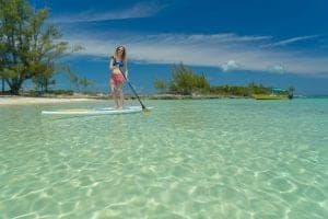 A woman on a standup paddlboard  in shallow clear waters near a beach on Eleuthera Island, yachts anchored in background.